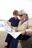 Little boy looking newspaper with grandpa