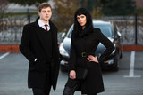 Young business couple against a car parking
