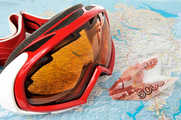 Alpine ski mask with airplane made from money on map