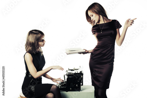 Two young women with a book and retro typewriter