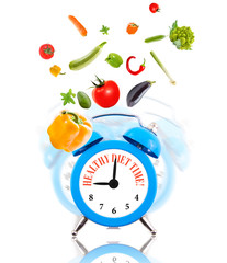 Diet concept, alarm clock ringing with vegetables.