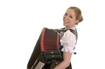 Hübsche blonde Frau im Dirndl spielt Akkordeon