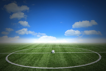 Soccer green grass field with blue sky white clouds background