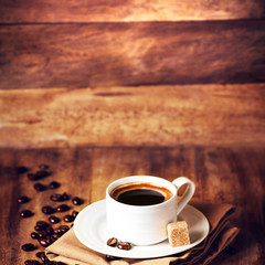 Cup of coffee with coffee beans on a beautiful wooden  brown bac