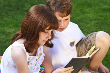 Students.Portrait of cute kids reading books  in natural environ