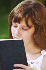 Pretty.Young beautiful girl reading a book outdoor