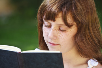 Read.Young beautiful girl reading a book outdoor