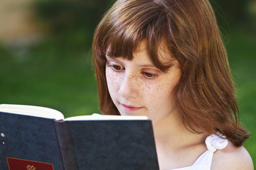 Literature.Young beautiful girl reading a book outdoor