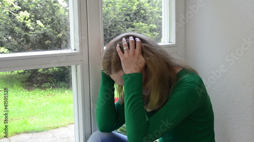 sad crouched woman sits on window sill.