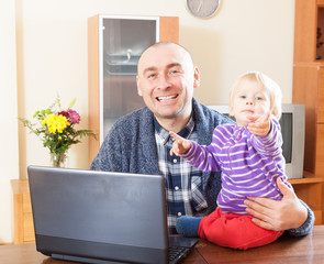 Father works at a computer  with daughter