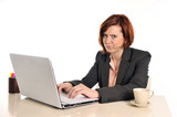 bored business red haired woman in stress at work with laptop