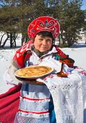 Shrovetide. Russian woman holding a plate with pancakes
