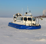 Hovercraft crossing frozen river in the sunny day