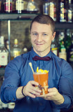 young man working as a bartender in a nightclub bar