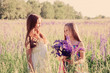 Two adorable girl with flowers outdoor