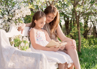 Happy mother with daughter with book in spring garden
