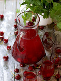 Сompote of cherries in a glass jug on a wooden background