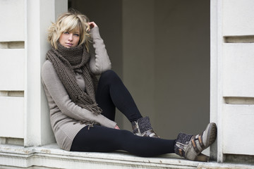 Attractive blonde young woman on window sill