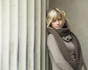 Attractive blonde young woman leaning against concrete column