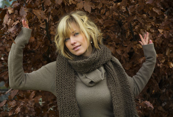 Attractive blonde young woman against autumn leaves