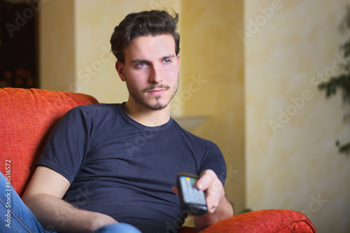 Handsome young man on counch, using TV remote control