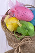 Easter decorative eggs in the basket on a light background