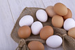 Brown and white fresh eggs on a light background