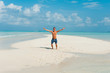 Happy attractive young male jumps on beach with white sand and o