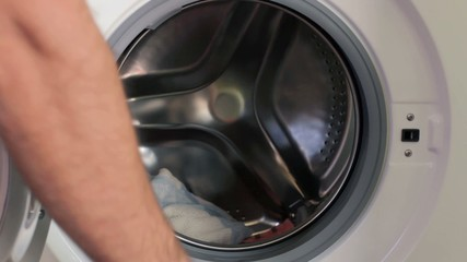 Placing dirty clothes in a washing machine