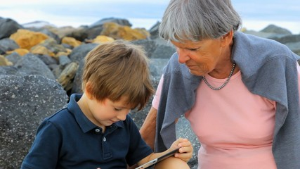 Happy kid playing with tablet with grandma