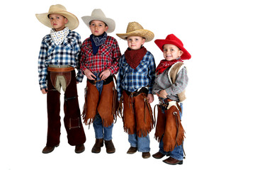 four cowboy brothers standing wearing hats and chaps