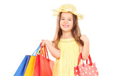 Cute girl in fancy clothes holding shopping bags