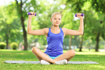 Female in park sitting on mat and exercising with dumbbells