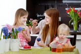 Mother and her daughters painting Easter eggs