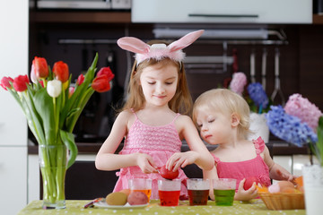 Two little sisters painting Easter eggs
