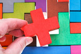 putting cross shaped block in wooden puzzle