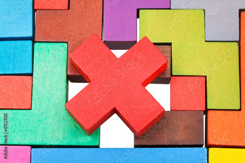 cross shaped piece on multicoloured puzzle
