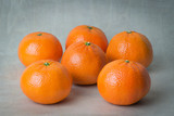 Six tangerines on a gray background