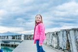 Outdoor portrait of a cute little girl in a bright pink jacket