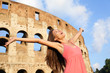 Happy carefree elated travel woman by Colosseum