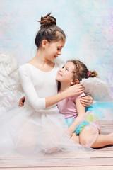 Elder ballet dancer hugging her little sister