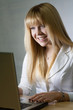beautiful girl laughing while chatting online with laptop