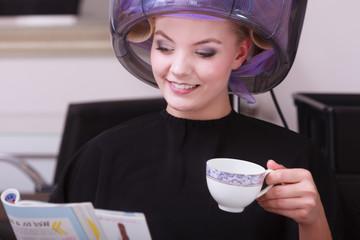 Girl reading magazine drinking coffee. Hairdryer in hair salon