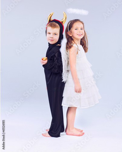 Cute little children as devil and angel