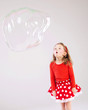Little girl making the soap bubbles