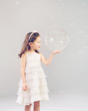 Funny lovely little girl playing with soap bubbles