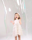 Cute child in the large soap bubble
