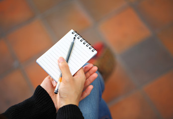 Woman hand with notepad and pen