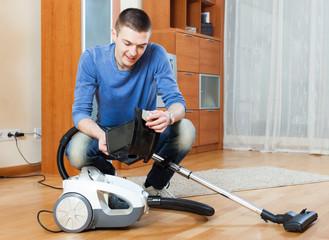 man  vacuuming with vacuum cleaner on parquet floor in living ro