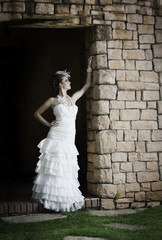 Vintage bride leaning against brick wall